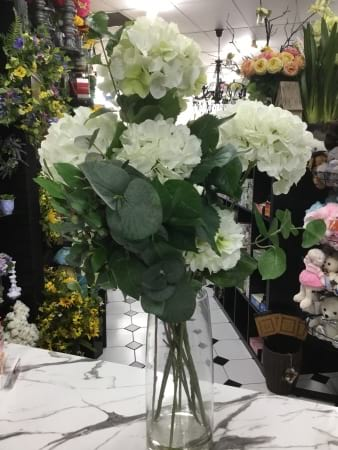 Artificial glass vase arrangement of white hydrangeas