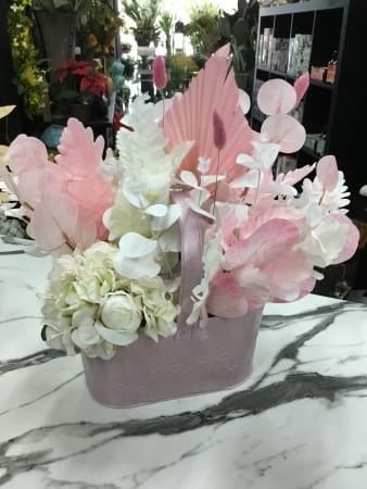 Pink and white artificial florals in metal giftbasket